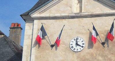 Französische Flaggen und Uhr am Gebäude